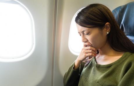 Frau mit Flugangst im Flugzeug. Wie Sie Ängste überwinden können.